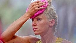 Die deutsche Siebenkämpferin Carolin Schäfer kühlt sich mit einem Eisbeutel den Kopf.