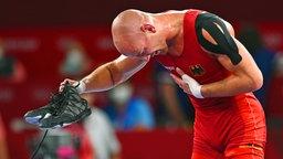 Der deutsche Ringer Frank Stäbler hält seine Schuhe hoch und jubelt über Bronze.
