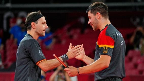 Die deutschen Tischtennis-Spieler Timo Boll (l.) und Patrick Franziska klatschen ab. © dpa-Bildfunk Foto: Vincent Thian/AP/dpa