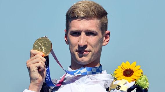 Der deutsche Schwimmer Florian Wellbrock präsentiert seine Goldmedaille im 10km Schwimmen. © dpd-bildfunk Foto: Oliver Weiken
