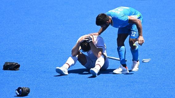 Varun Kumar (r) aus Indien tröstet Lukas Windfeder aus Deutschland nach dem Ende der Hockey-Partie. © dpa-bildfunk Foto: Swen Pförtner