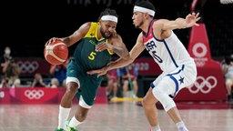 Patty Mills von Australien dribbelt an Devin Booker aus den USA mit dem Basketball vorbei.