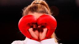 Die ukrainische Karateka Anschelika Terliuga formt mir ihren Handschuhen ein Herz.