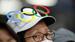 Ein Zuschauer bei den Olympischen Spielen trägt eine Mütze auf dem Kopf, auf der die olympischen Ringe zu sehen sind.