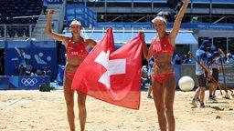 Die beiden Volleyballspielerinnen Anouk Verge-Depre und Joana Heidrich feiern Bronze mit der Schweizer Flagge.