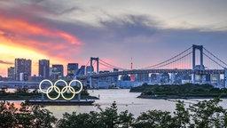 Ein Blick auf olympischen Ringe vor der Rainbow Bridge bei Sonnenuntergang.