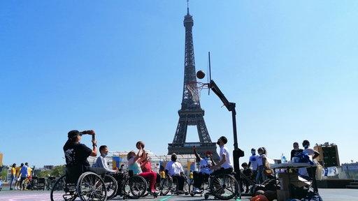 Menschen in Rollstühlen spielen Basketball vor dem Eifelturm in Paris.