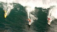 Drei Surfer reiten eine Welle vor Hawaii © imago/ZUMA Press