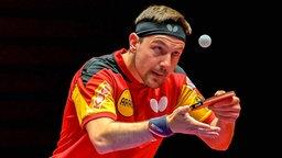 Tischtennisspieler Timo Boll konzentriert sich beim Aufschlag auf den Ball.